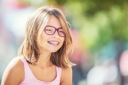 歯科ブレースとメガネの幸せな笑顔の女の子。若いかわいい白人金髪の女の子は歯ブレースとメガネを着用します。
