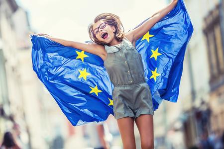 EU-Flagge. Nettes glückliches Mädchen mit der Flagge der Europäischen Union. Junge Teenager-Mädchen winken mit der Flagge der Europäischen Union in der Stadt.