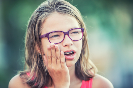 Portrait of young teen girl with toothache. Girl with dental braces and glasses.