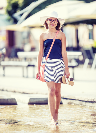 Cute little young teen girl walking on the fountain in hot summer day.