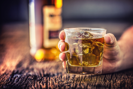 Alcoholism.Hand alcoholic and drink the distillate whiskey brandy or cognac. Stock Photo