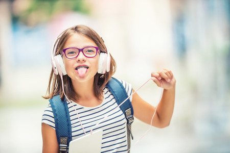 Schoolgirl with bag, backpack. Portrait of modern happy teen school girl with bag backpack headphones and tablet. Girl with dental braces glasses and tongue out.