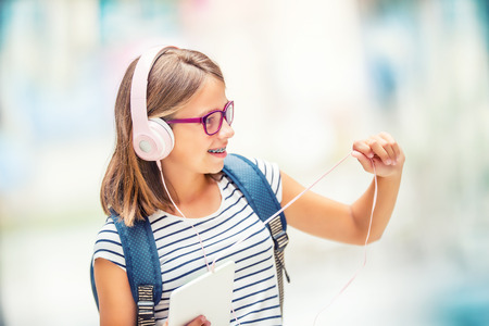 Schoolgirl with bag, backpack. Portrait of modern happy teen school girl with bag backpack headphones and tablet. Girl with dental braces and glasses.
