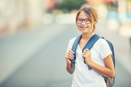 Schoolgirl with bag, backpack. Portrait of modern happy teen school girl with bag backpack. Girl with dental braces and glasses. Stockfoto