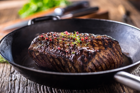 Beef steak. Juicy Rib Eye steak in pan on wooden board with herb and pepper.