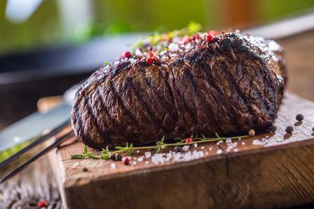 grill: Beef steak. Juicy Rib Eye steak in pan on wooden board with herb and pepper.