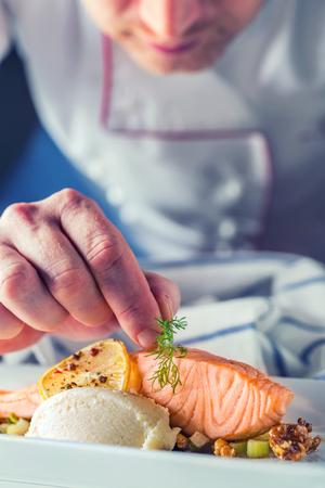 ホテルやレストランの台所の料理、シェフの手のみ。ノルウェー サーモンのムニエル ディル装飾を準備しました。 写真素材