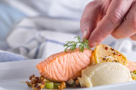 Chef-kok in het hotel of restaurantkeuken koken, alleen handen. Bereide zalm steak met dille decoratie.