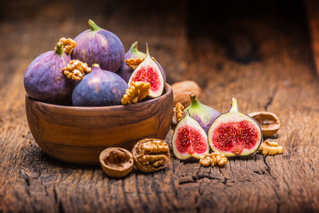 Figs and walnuts.. A few figs and walnuts in a bowl on an old wooden background.