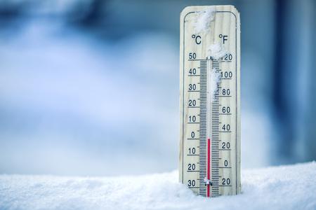 Un thermomètre sur la neige indique des températures basses - zéro. Températures plus basses en degrés Celsius et fahrenheit. Temps froid en hiver - zéro degrés Celsius trente-deux.