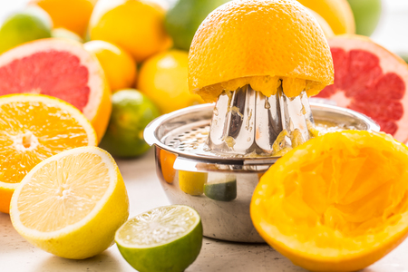 Preparation of orange grape or multivitamin juice, hands squeeze juice on a manual metal juicer surrounded by fresh tropical fruit.