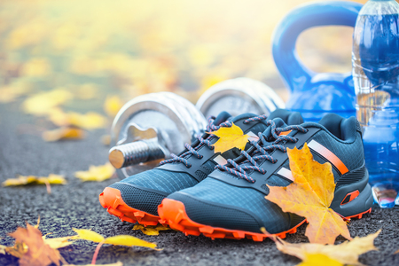 Pair of blue sport shoes water and  dumbbells laid on a path in a tree autumn alley with maple leaves -  accessories for run exercise or workout activity.