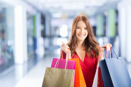 Beautiful happy girl with credit card and shopping bags in shopping mall. Shopping Center in the background.  Stock Photo