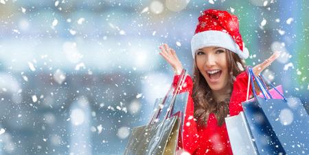 Compras de Navidad. Atractiva chica feliz con tarjeta de crédito y bolsas de compras en el sombrero de santa. Ambiente nevado.