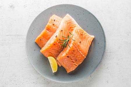 Salmon. Raw salmon steaks herb peper lemon on white concrete background.