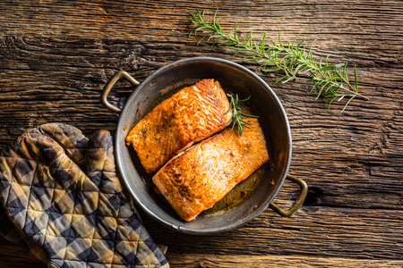 Salmon. Two juicy salmon steaks in roast pan with herb decoration on rustic oak table.