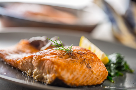 Salmon Roast Fillet. Portion of roast salmon fillet with spinach mushrooms in restaurant pub home or hotel.