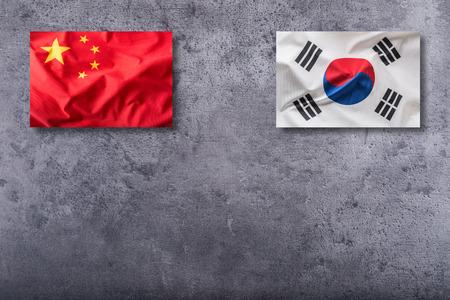 China and South korea flag on concrete background.
