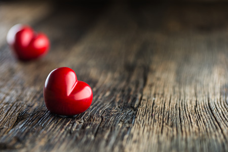 Valentines red heart. One two red heart on wooden table. Wedding or valentine day. Stock Photo