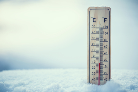 Thermometer on snow shows low temperatures under zero. Low temperatures in degrees Celsius and fahrenheit. Cold winter weather ten under zero.