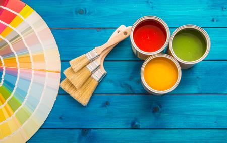 Tavolozza di colori di lattine di vernice, lattine aperte con pennelli sul tavolo blu. Archivio Fotografico - 96015967