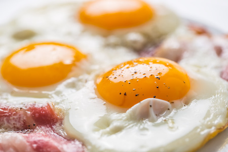 Ham and Eggs. Bacon and Eggs. Salted egg with pepper on white plate. English breakfast. Archivio Fotografico