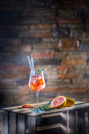 Cocktail drink on a old  wooden board. Alcoholic beverage with tropical fruits red pepper herb and ice. Stock Photo
