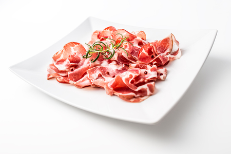 Prosciutto. Curled slices of delicious italian prosciutto with rosemary. Stock Photo