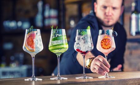 Barman in pub of restaurant die een gin tonic cocktaildranken in wijnglazen voorbereiden.