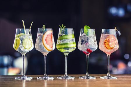 Cinco coloridos cócteles de gin tonic en copas de vino en barra de bar en pup o restaurante.