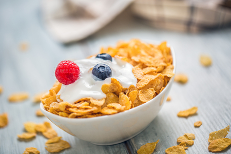 Cornflakes. Dish of cornflakes with yogurt blueberries and raspberries on kitchen table.