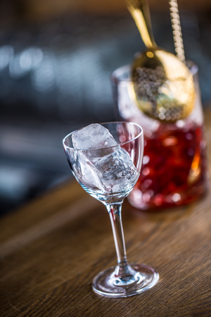 Manhattan cocktail drink decorated on bar counter in pub or restaurant. Ice cube in empty glass. Stock Photo