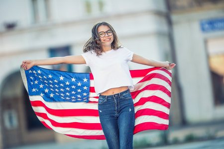 Happy young american school girl holding and waving in the city with USA flag.