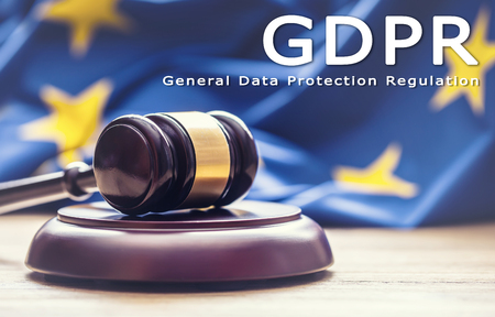 Judges wooden gavel with EU flag in the background with text GDPR- General Data Protection Regulation.