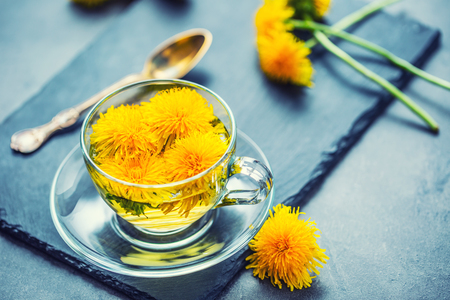 Cup of dandelion tea on slate board. Stock Photo