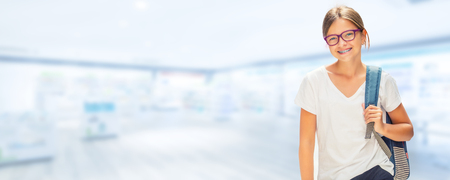 Portrait of modern happy teen school girl with bag backpackand on blurred background. Girl with dental braces and glasses.