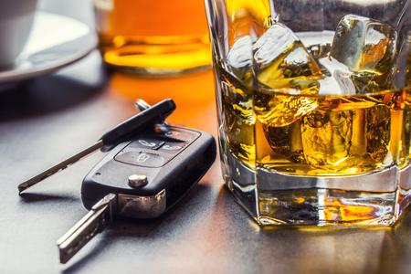Llaves del coche y vaso de alcohol en la mesa en un pub o restaurante.