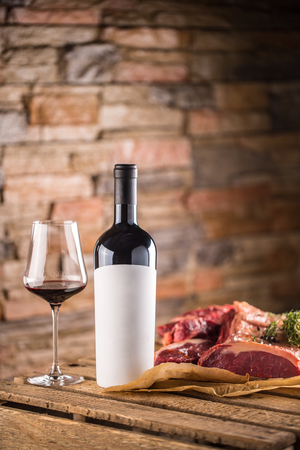 Cup and a bottle of red wine and raw beef steak on wooden table.