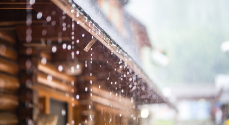 Downpour in the summer storm and rain drops on the roof. 免版税图像