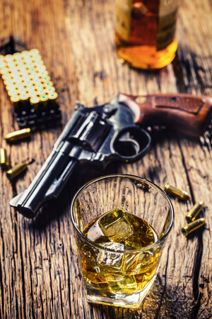 Glass of whiskey cognac or bourbon with revolver and bullets on wooden table.