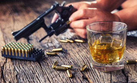 Man hands holding gun and alcohol glass on the table.