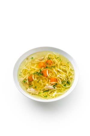 Chicken or beef soup with noodles carrot and parsley herb isolated on white.