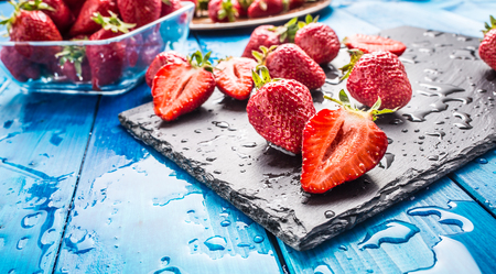 Fresh ripe strawberries washed with water on blue table.