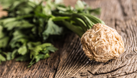 Fresh celery root with leaf on rustic oak table. Stock Photo