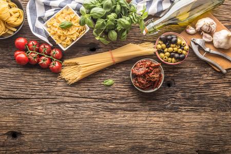 Italian food ingredients pasta olive oil parmesan cheese basil garlic mushrooms tomatoes olives on wooden table. Standard-Bild