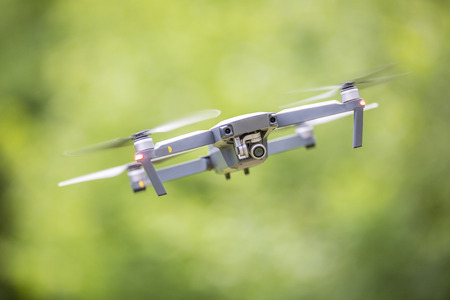 Close-up quadcopter drone with camera flying in park. Stock fotó