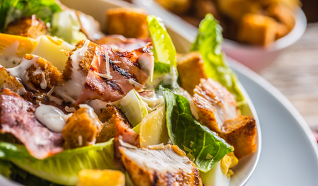 Delicious salad caesar with grilled chicken breast croutons eggs bacon parmesan cheese and  lettuce with dressing. 스톡 콘텐츠