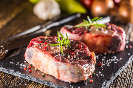 Two pieces raw beef shank on slate board and wooden table.. Archivio Fotografico