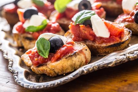 Toast bruschetta avec mozzarella tomates olives basilic et huile d'olive. Ingrédients caprese et cuisine italienne ou méditerranéenne.