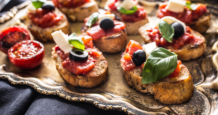 Bruschetta toast with mozzarella tomatoes olives basil and olive oil. Caprese ingredients and italian or mediterrannean cuisine.